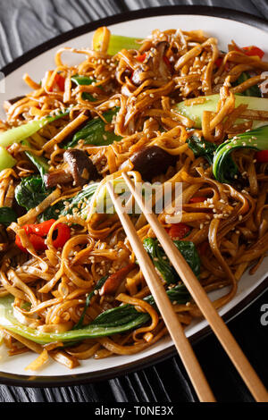 Stir fry of udon noodles with pak choi and shiitake mushrooms close-up on a plate. vertical - Stock Photo