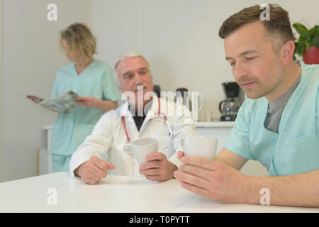 portrait of smiling doctors having a coffee break - Stock Photo