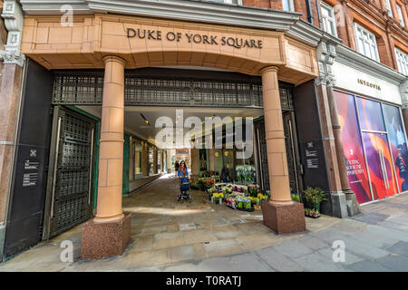 A woamn pushing a buggy walks past a florist shop at the entrance to Duke of York Square,Sloane Square , Chelsea, London SW3 - Stock Photo
