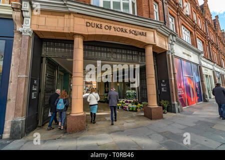 People walking through the entrance to Duke of York Square,Sloane Square , Chelsea, London SW3 - Stock Photo