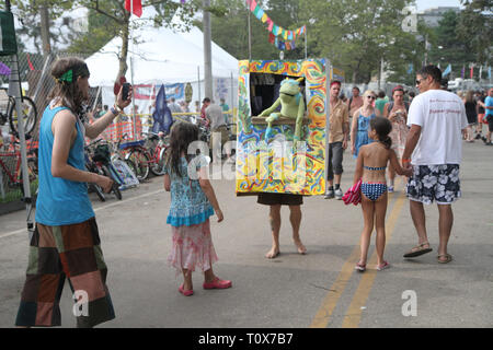 Concert goers are shown being entertained my a 'Walking Puppet Theater' during an outdoor concert festival. - Stock Photo