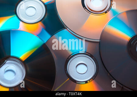 Close-up of a pile of CD or DVD discs with colored reflections - Stock Photo