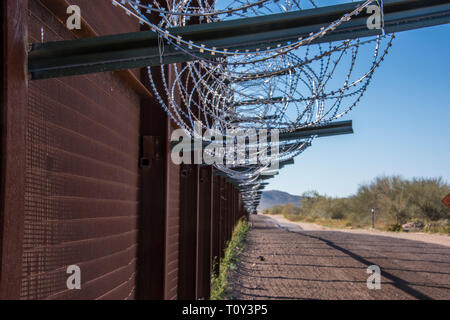 Border Fence with Razor Wire along the International Border between United States and Mexico on the east side of Highway 85 at Lukeville, Arizona. - Stock Photo