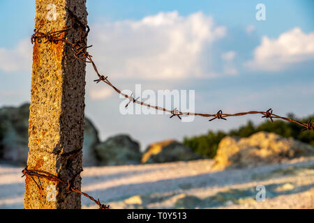 Weathered concrete pillar with rusty barbed wire on a natural background, the fence of the Stone Mushrooms near Beli Plast village, Bulgaria, close pa - Stock Photo