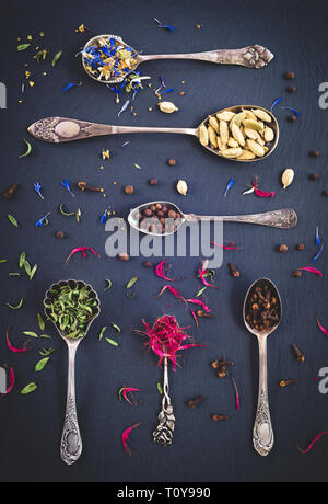Silver spoons full of spices, herbs and floral teas, on black slate background. - Stock Photo