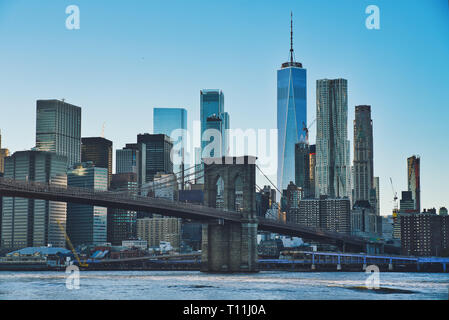 Photo of the Manhattan at the sunset time with the Brooklyn Bridge - Stock Photo