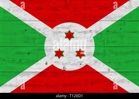 Burundi flag painted on old wood plank. Patriotic background. National flag of Burundi - Stock Photo