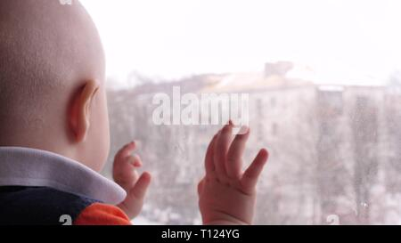 Happy baby looks out the window. The child rejoices smiling. Draws a hand on the window. Slow Motion. - Stock Photo