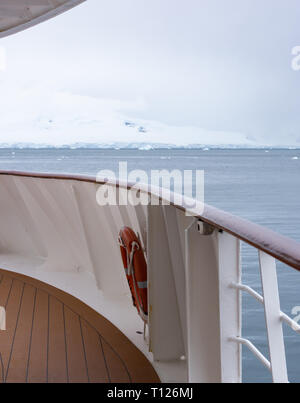 A ship's wooden deck, wood and metal handrail and life preserver in the foreground and a glacier on Antarctica in the background. - Stock Photo