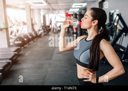 Close up of a beautiful girl drinking water from the bottle. He is having some rest after workout. Cut view. - Stock Photo