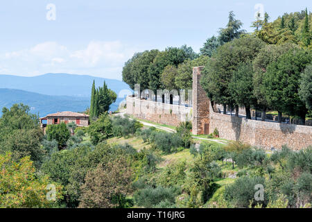 Montalcino wall walled fortress city in Italy Val D'Orcia countryside in Tuscany hilltop small town village in summer stone house and park with mounta - Stock Photo
