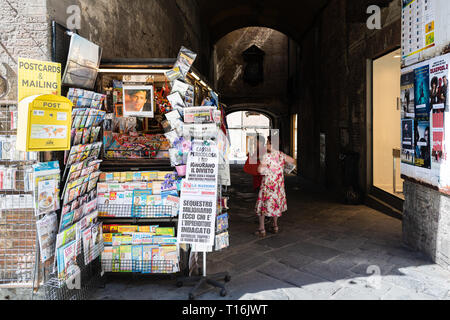 Siena, Italy - August 27, 2018: Historic medieval old town village in Tuscany with shopping souvenirs and map tour travel guide street vendor retail d - Stock Photo