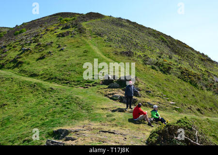 Walkers having a rest on a hilly route along the coast, having walked up from Heddon Valley, Devon, UK - Stock Photo