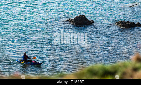 Bray Head, Ireland. 24th March, 2019 Kayaker enjoying calm, warm weather having rest on his passage from Greystones to Bray and looking at cliff's wildlife. Credit: Vitaliy Tuzov/Alamy Live News - Stock Photo