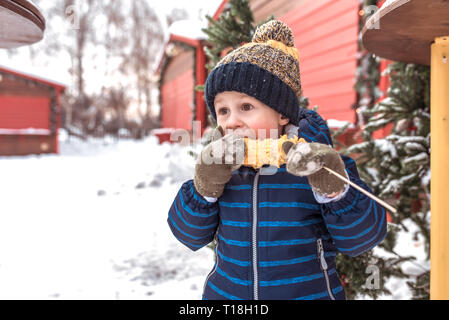 A little boy is 4-5 years old, in the winter in the city in the fresh air. He eats boiled corn. Breakfast lunch and snacks on weekends on a cold - Stock Photo