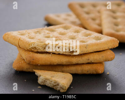 stack of square crackers with pieces and crumbs on slate gray background. Dry salt cracker cookies with fiber and dry spices - Stock Photo