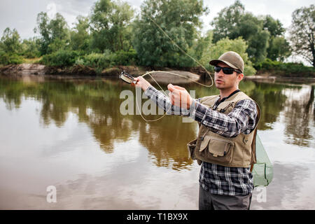 A picture of man stands in water and waving with fly rod. He is going to fish. Guy has fishing net on the back. He looks serious and calm. - Stock Photo