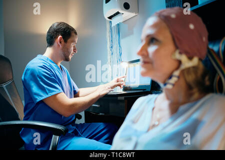 Doctor Doing Brain Medical Exam On Old Woman In Hospital - Stock Photo