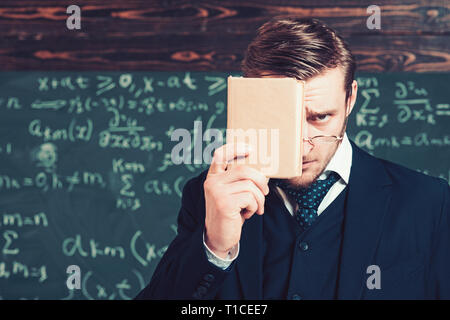 Young man in suit covering his face with book. Closeup portrait of young blond aristocrat with stylish hair and beard - Stock Photo