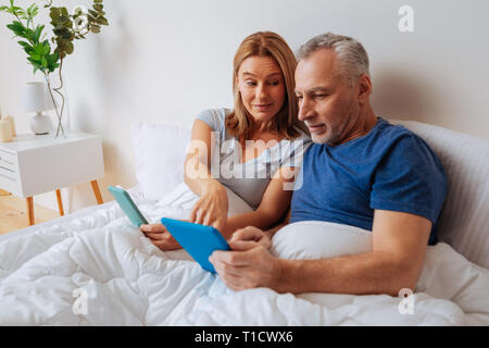 Wife recommending best variant for husband shopping online - Stock Photo