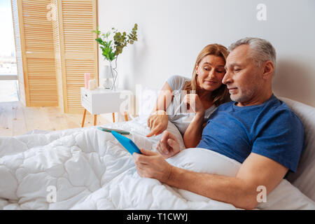 Wife showing the best option for husband shopping online - Stock Photo