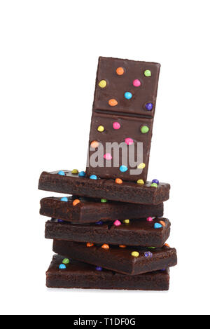 pile of chocolate fudge brownies with candy pieces on white - Stock Photo