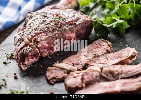 Freshly grilled tomahawk steak on slate plate with salt pepper rosemary and parsley herbs. Sliced pieces of juicy beef steak - Stock Photo