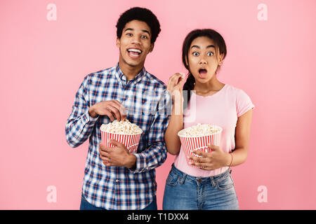 African-american couple eating popcorn on pink background - Stock Photo