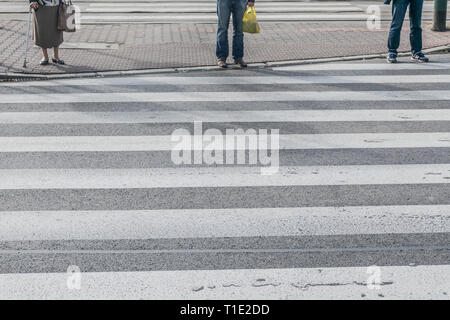 Pedestrians waiting to cross on the road, feet rushing through the zebra traffic walk way - Stock Photo