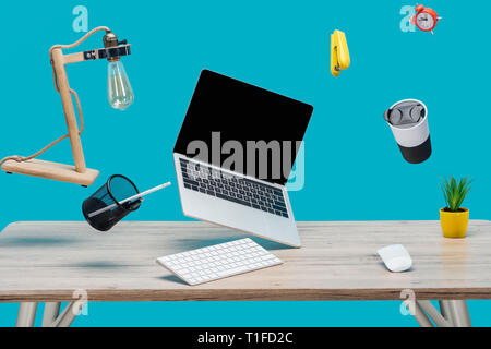 laptop with blank screen and stationery levitating in air at workplace isolated on turquoise - Stock Photo