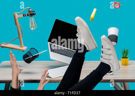 cropped view of woman levitating in air with laptop and stationery at workplace isolated on turquoise - Stock Photo