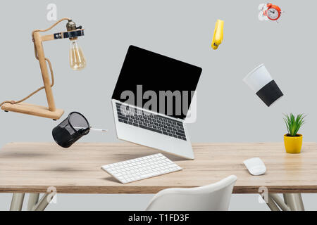 laptop with blank screen and stationery levitating in air at workplace isolated on grey - Stock Photo