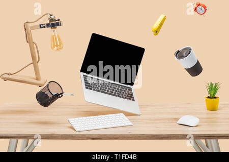 laptop with blank screen and stationery levitating in air at workplace isolated on beige - Stock Photo