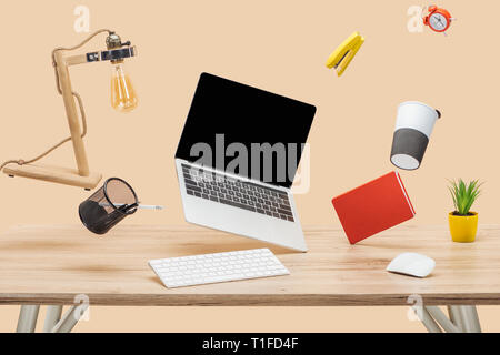 laptop with blank screen and stationery levitating in air above wooden desk isolated on beige - Stock Photo