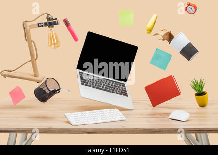 laptop with blank screen, thermomug with coffee splash and stationery levitating in air above wooden desk isolated on beige - Stock Photo