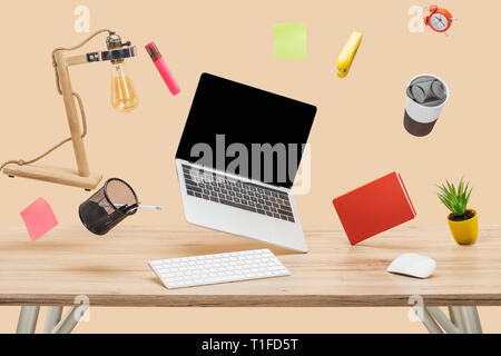 laptop with blank screen, lamp, sticky notes and stationery levitating in air above wooden desk isolated on beige - Stock Photo