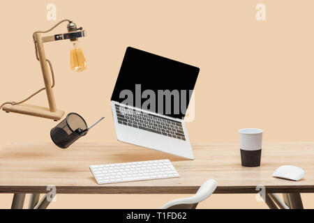 laptop with blank screen, lamp and stationery levitating in air above wooden desk isolated on beige - Stock Photo