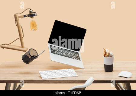 laptop with blank screen, lamp and stationery levitating in air above wooden desk with thermomug with coffee splash isolated on beige - Stock Photo