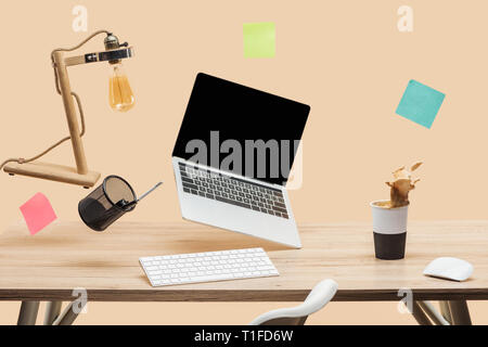 laptop with blank screen, lamp, empty sticky notes and stationery levitating in air above wooden desk with thermomug with coffee splash isolated on be - Stock Photo