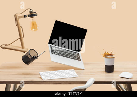 laptop with blank screen and lamp levitating in air above wooden desk with thermomug with coffee splash isolated on beige - Stock Photo