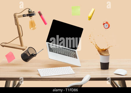 laptop with blank screen, lamp, empty sticky notes and stationery levitating in air above workplace with thermomug with coffee splash  on table isolat - Stock Photo