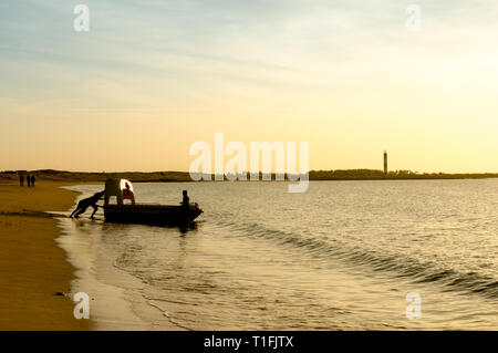 Silhouette of men pulling a boat into the sea at a beach in Gujarat - Stock Photo