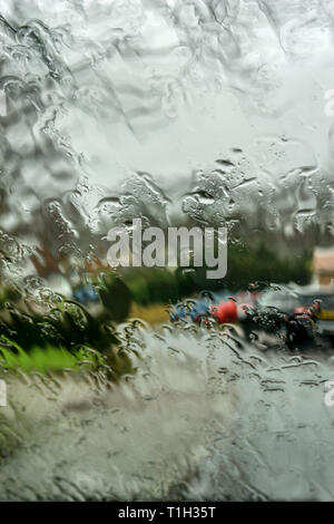 Rain on wet car windscreen with out of focus suburban residential street in background. - Stock Photo
