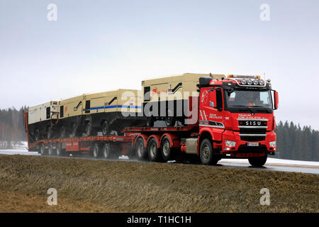 Humppila, Finland - March 23, 2019: Sisu Polar truck transports three Ingersoll Rand air compressors on trailer along highway on a rainy day of spring - Stock Photo
