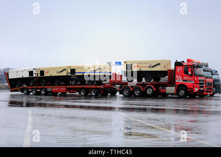 Forssa, Finland - March 23, 2019: Sisu Polar truck with a load of three Ingersoll Rand air compressors on a truck stop in rain, side view. - Stock Photo