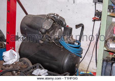 Air compressor in car mechanic workshop. Old round air compressor in mechanic workshop - Stock Photo