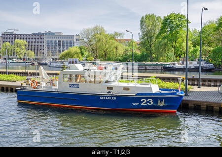 Berlin, Germany - April 22, 2018: Water guard police boat entering the Multi-chamber Muehlendamm locks in the central Mitte district - Stock Photo