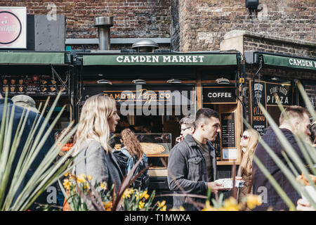 London, UK - March 23,2019: People walking past pizza food stall inside Camden Market, London. Started with 16 stalls in March 1974, Camden Market is  - Stock Photo