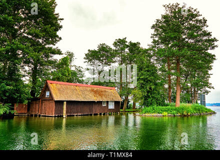 Old wooden boat house with thatched roof in an idyllic location on Lake Schwerin. Mecklenburg-Vorpommern Germany - Stock Photo