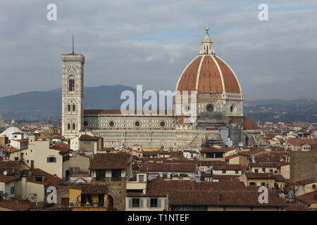 Florence Cathedral (Duomo di Firenze) and the Giotto's Campanile (Campanile di Giotto) rising over the tiled roofs of the Florence downtown pictured from the rooftop terrace of the Palazzo Vecchio in Florence, Tuscany, Italy. - Stock Photo